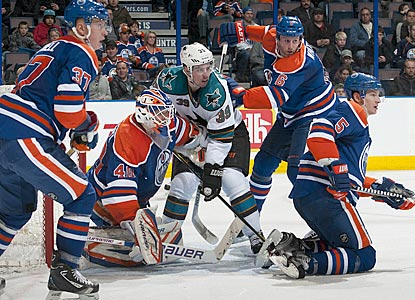 Logan Couture (39) draws plenty of attention as he tries to establish position in front of Edmonton goalie Devan Dubnyk.  (Getty Images)