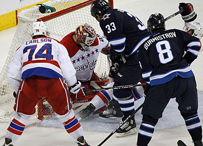 Dustin Byfuglien crashes the net and forces the puck past Tomas Vokoun for what turns out to be the winning goal. (AP)