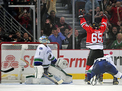 Andrew Shaw deflects the puck past Roberto Luongo and celebrates the victory against Vancouver. (US Presswire)
