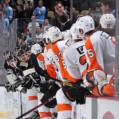 Penguins and Flyers players keep watch while assistant coaches Tony Amonte and Craig Berube exchange words.  (Getty Images)