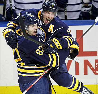 Derek Roy (9) celebrates with Marcus Foligno after scoring the game-winning goal in overtime against the Maple Leafs. (AP)