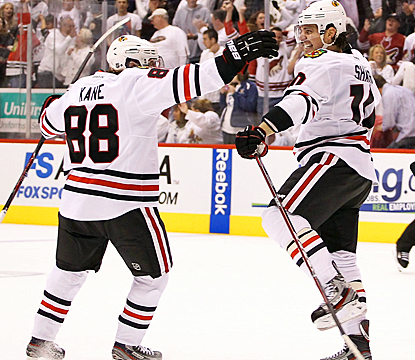 Patrick Sharp (right) celebrates with Patrick Kane after scoring the game-tying goal with just 5.5 seconds left in regulation. (Getty Images)