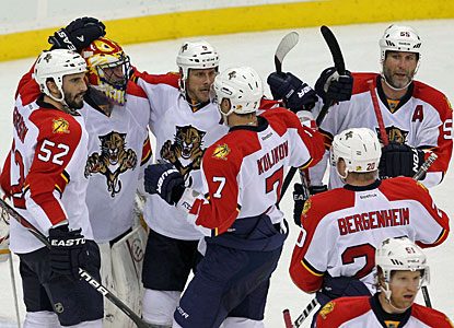 Panthers players surround backup and former Devils goalie Scott Clemmensen, who wins in relief. (US Presswire)