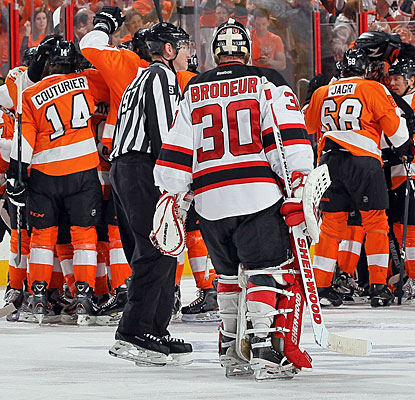 The Flyers celebrate their Game 1 overtime victory as Devils goalie Martin Brodeur has words with a linesman.  (Getty Images)