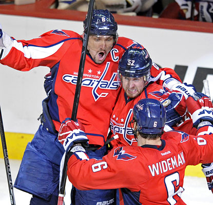 Alex Ovechkin and Dennis Wideman surround Mike Green after the defenseman's go-ahead PP goal with 5:48 to go.  (AP)