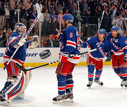 Henrik Lundqvist is pumped and cheered by his teammates after stopping 22 shots in the decisive game. (Getty Images)