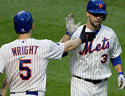 Dillon Gee is greeted by David Wright after scoring a run on a double by Mike Baxter. (AP)