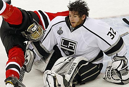 Kings goalie Jonathan Quick, who is once again brilliant in net, loses his mask in an overtime collision.  (US Presswire)
