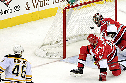 David Krejci (left) watches as his shot beats Cam Ward (right) for the tiebreaking goal. (Getty Images)