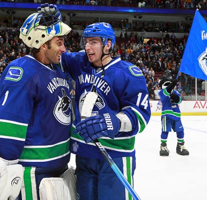 Roberto Luongo (left) celebrates with Alexandre Burrows after recording the shutout and the win.  (Getty Images)