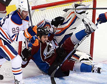 Avs winger Patrick Bordeleau crashes into Edmonton goalie Devan Dubnyk, who records 37 saves.  (US Presswire)