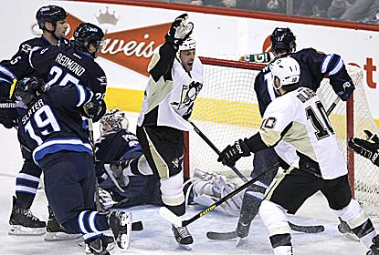 Pittsburgh's Craig Adams scores two goals, including an empty-netter in the final moments, to help Pittsburgh drop Winnipeg. (AP)