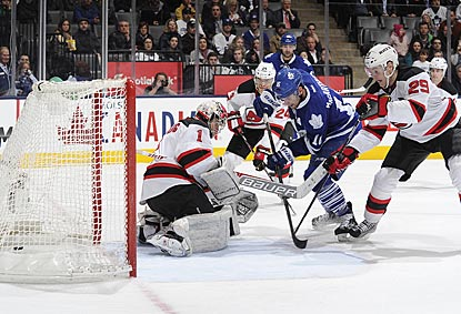 Toronto's Clarke MacArthur scores the go-ahead goal in the third period past Johan Hedberg despite Mark Fayne's defense.  (Getty Images)