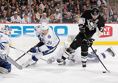 Evgeni Malkin skates cross-ice between two Lightning defenders before scoring the tying goal in the third period.  (Getty Images)