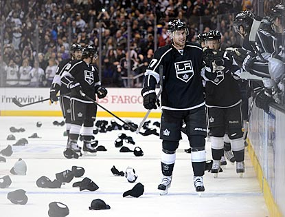 Jeff Carter (front) accepts congratulations from his teammates on his hat trick while giveaway hats rain down upon the ice.  (Getty Images)