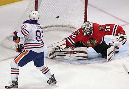 Sam Gagner puts the puck past Chicago's Ray Emery in the first period, during which he scores two of Edmonton's four goals.  (Getty Images)