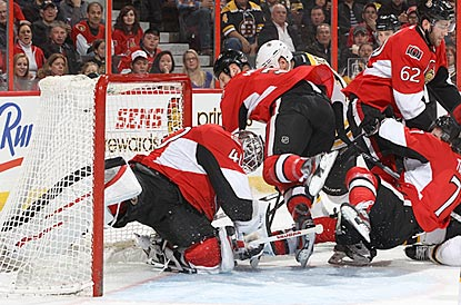 A host of Ottawa Senators help goaltender Robin Lehner prevent Boston's Milan Lucic (rear) from scoring.  (Getty Images)