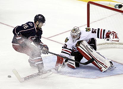 Corey Crawford pokes the puck away from Columbus' Derick Brassard to clinch a shooutout victory for Chicago.  (AP)