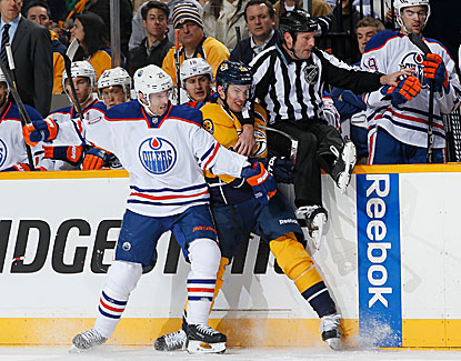 Edmonton's Eric Belanger and Nashville's Roman Josi get caught in a jam along the boards with linesman Don Henderson. (Getty Images)