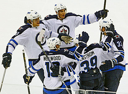Evander Kane (top) and the Jets celebrate after Tobias Enstrom (39) scores against the Hurricanes. (AP)