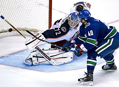 Maxim Lapierre (right) sends a shot past Blue Jackets goalie Sergei Bobrovsky for the winning goal. (AP)