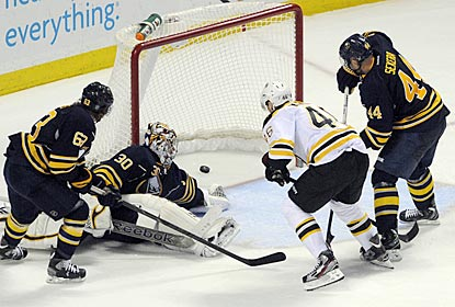 Bruins center David Krejci (46) opens the scoring despite the efforts of goalie Ryan Miller and two Sabres teammates.  (AP)