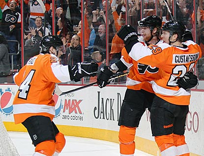 Erik Gustafsson (right) gets mobbed after scoring the go-ahead goal only 90 seconds after the Flyers tie the game.  (Getty Images)