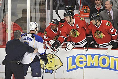 The Blues-Blackhawks rivarly is an intense one. A trainer holds back Barret Jackman during a midgame confrontation.  (AP)