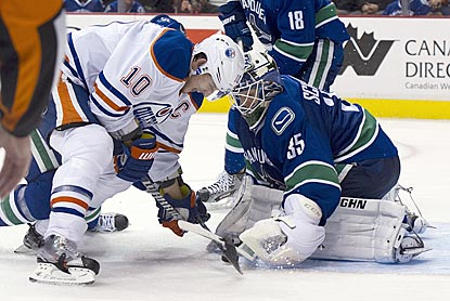 Edmonton's Shawn Horcoff tries to jam the puck past Vancouver's Cory Schneider during the third period.  (Getty Images)