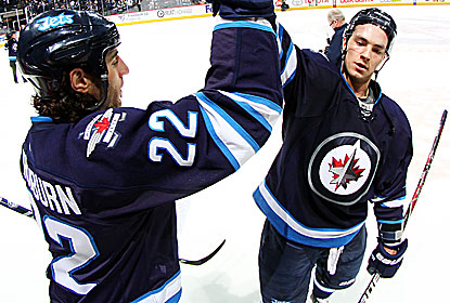 Chris Thorburn and Alex Burmistrov celebrate after the Jets use a big second period to end their five-game skid. (Getty Images)