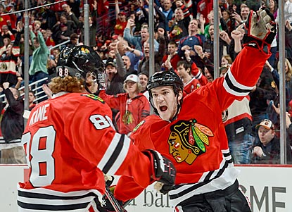 Patrick Kane (left) is the first to reach Andrew Shaw after assisting on Shaw's go-ahead goal early in the third period.  (Getty Images)
