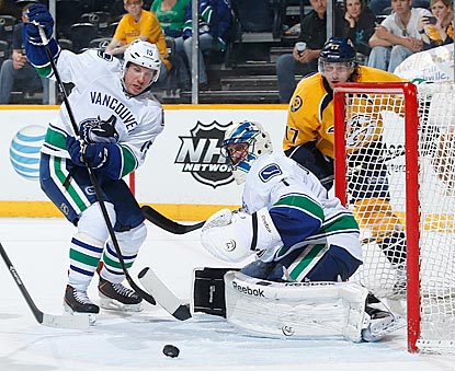 Vancouver's Derek Roy (left) and Roberto Luongo follow a loose puck. Luongo stops 36 of 38 shots to earn the victory.  (Getty Images)