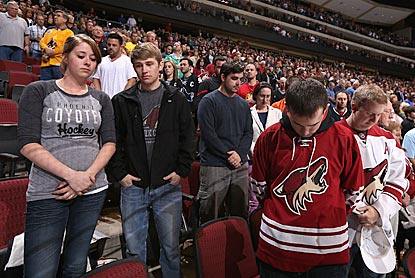 Fans at the Sharks-Coyotes game in Glendale, Ariz., observe a moment of silence for the victims at the Boston bombings.  (Getty Images)
