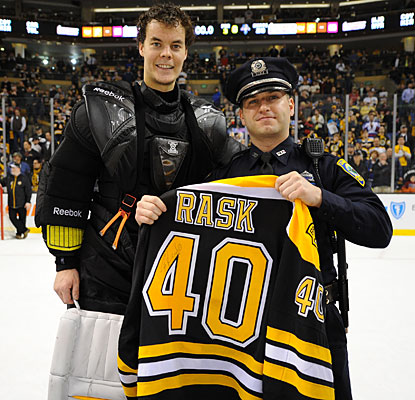 After recording his fourth shutout of the season, Tuukka Rask gives his signed shirt to a Cambridge, Mass., police officer.  (Getty Images)