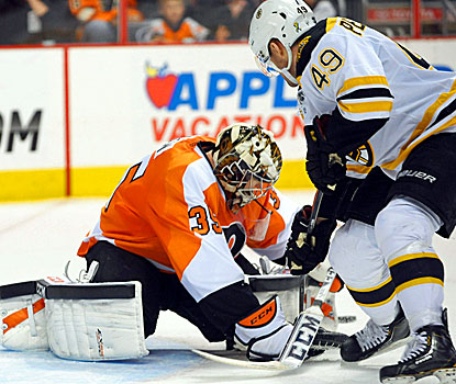 Flyers goalie Steve Mason (left) makes a save against Bruins center Rich Peverley. (USATSI)