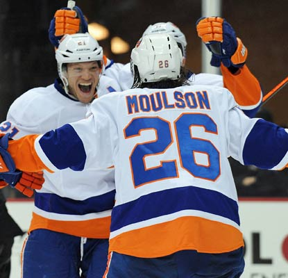 Kyle Okposo (left) scores the game-winner with 7:37 left in the game to cap New York's comeback.  (Getty Images)