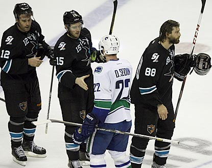 Daniel Sedin (22) exchanges post-series handshakes with the Sharks, including Patrick Marleau (left), who scores the winner.  (USATSI)