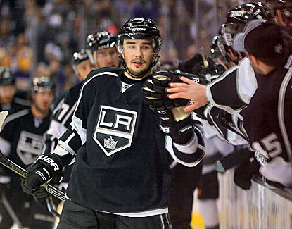 Slava Voynov, who scores the deciding goal and registers an assist, high-fives Kings players on the bench. (Getty Images)
