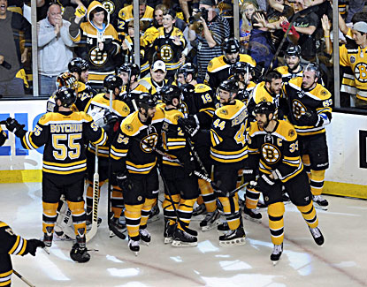 Bruins players mob Patrice Bergeron moments after he scores the winning goal in double overtime to give Boston a 2-1 win. (USATSI)