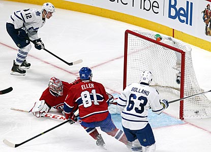 Mason Raymond (left) puts the puck past Montreal goalie Carey Price to increase Toronto's lead to 4-2 in the third period.  (USATSI)