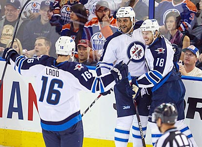 Andrew Ladd (16) and Dustin Byfuglien congratulate Bryan Little (18) on his goal in the first period.  (USATSI)