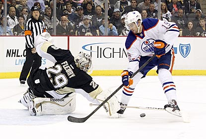 Marc-Andre Fleury pokes the puck away from Justin Schultz as he moves in on goal during the first period.  (USATSI)