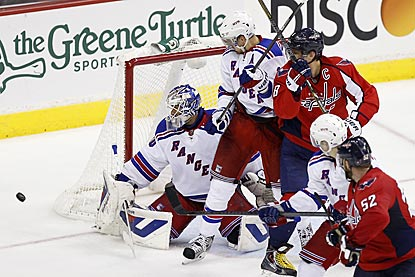 Henrik Lundqvist turns a shot aside in the third period as Marc Staal (center) defends against Alex Ovechkin.  (USATSI)