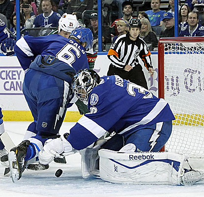 Lightning goalie Ben Bishop makes a save against Minnesota's Kyle Brodziak, one of his 25 in the game. (USATSI)