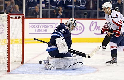 Martin Erat puts the puck through Ondrej Pavelec's pads to win the shootout for Washington.  (USATSI)