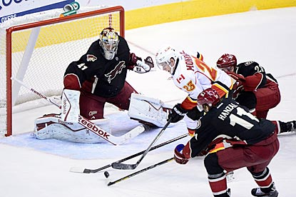 Phoenix goaltender Mike Smith and teammates thwart Calgary center Sean Monahan during the third period.  (USATSI)