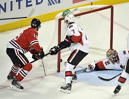 Jonathan Toews (left) taps in the puck past Craig Anderson to complete his third NHL hat trick and put Chicago ahead 5-4.  (USATSI)