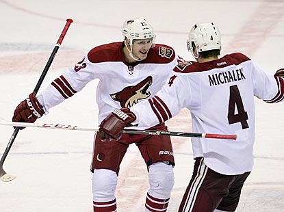 Phoenix defenseman Zbynek Michalek (4) is the first to congratulate Oliver Ekman-Larsson on his overtime goal.  (USATSI)