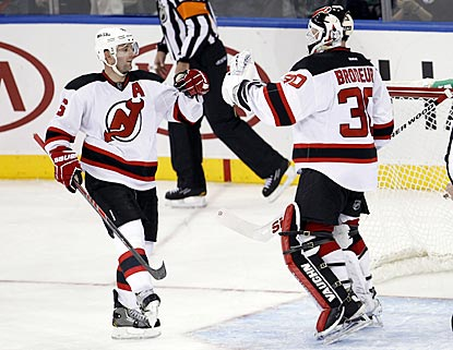 Andy Greene congratulates Martin Brodeur, who makes 33 saves and earns his 48th career victory against the Rangers.  (USATSI)