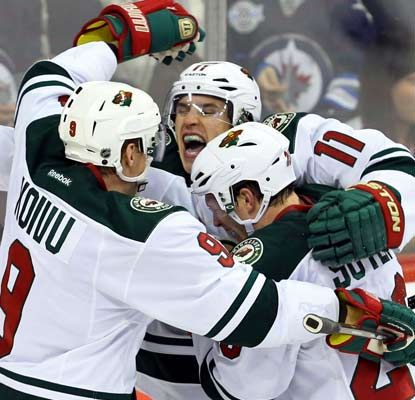 Zach Parise's (center) 11th goal of the season for Minnesota sends the game into overtime.  (USATSI)